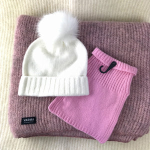 Pink woollen throw and childrens snood and white soft wool beanie with a fake fur pom pom