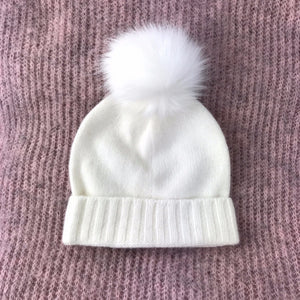 white baby hat with white pom pom