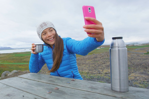 young woman wearing white Varma wool hat taking selfie with hot coffee
