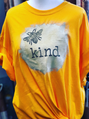 bee kind yellow t-shirt with a bee and the word kind on a cream painted circle
