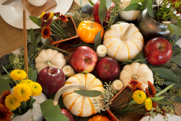 Thanksgiving tablescape created with pumpkins and red apples
