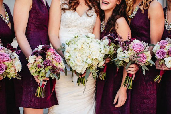 Bridesmaids holding bouquets in plum wedding theme
