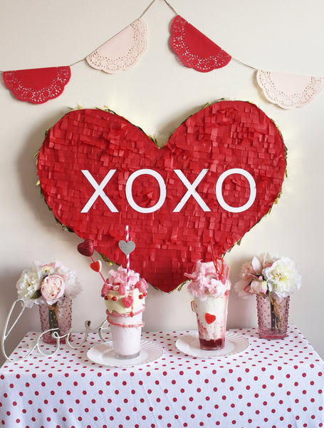 Table with Valentine's shakes and a red mache heart reading 'XOXO' on wall behind
