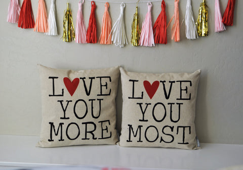"Pair of pillows reading ""Love You More' and 'Love You Most'"