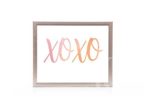 Wood-framed print of 'XOXO' in pink and orange