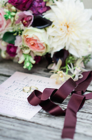 Plum wedding theme bouquet on rustic table