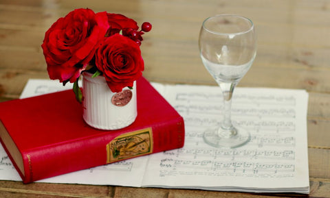 Red Valentine's day arrangement in mug next to wine glass
