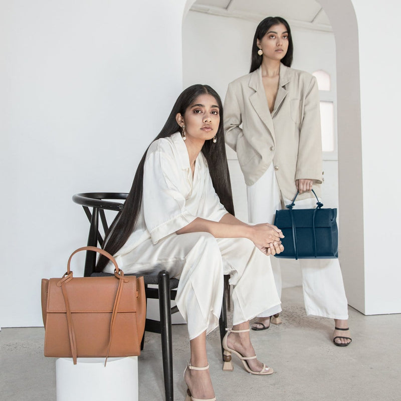 A woman wearing all white sitting in a chair, a rectangle genuine tan leather work bag and handbag with leather tassels, front flap and handle placed in the foreground. Another woman wearing a beige blazer standing in the background holding a rectangle navy blue genuine leather handbag with leather tassels, flap and handle.