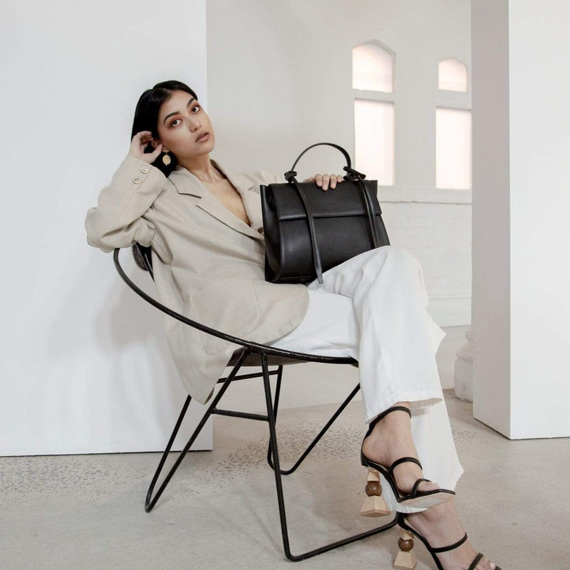 Full body shot of a woman leaning back in a chair holding rectangle genuine black leather handbag in a bright indoor setting.