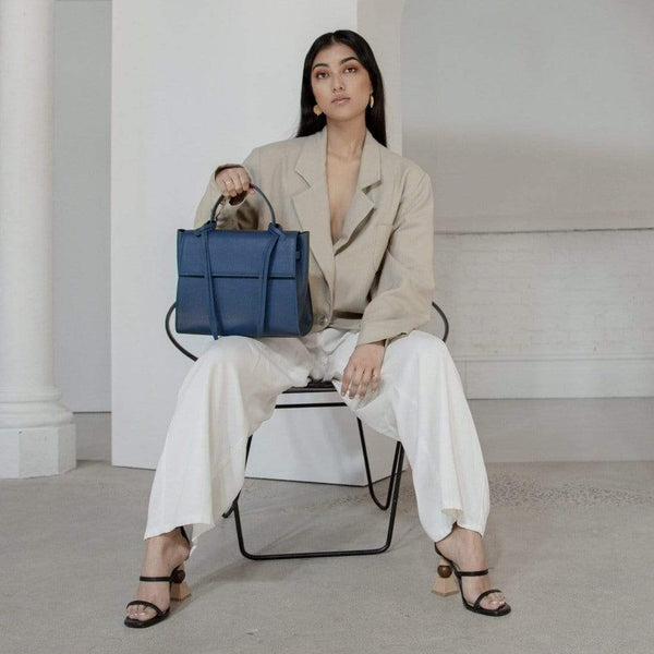 A woman wearing a beige blazer and white pants sitting in a chair, holding a navy blue leather handbag with leather tassels and flap by the handle.