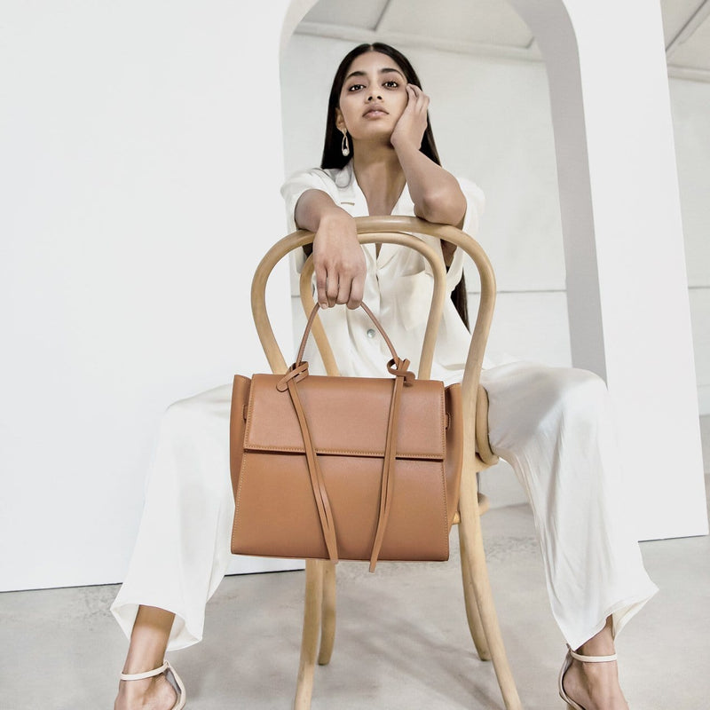 A woman wearing all white sitting in a chair, one hand on cheek, holding a rectangle genuine tan leather work bag and handbag with leather tassels, front flap and handle in the other hand to the front.
