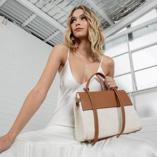 Low angle shot of a woman looking into the distance and holding the tan leather and natural canvas fabric bag with tan leather tassel, front flap and handle, in a all white setting.