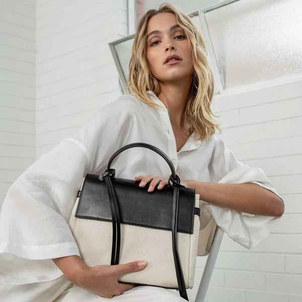 Half body shot of woman wearing white and posing with a black leather and natural canvas fabric trapezoid bag against a white brick wall.