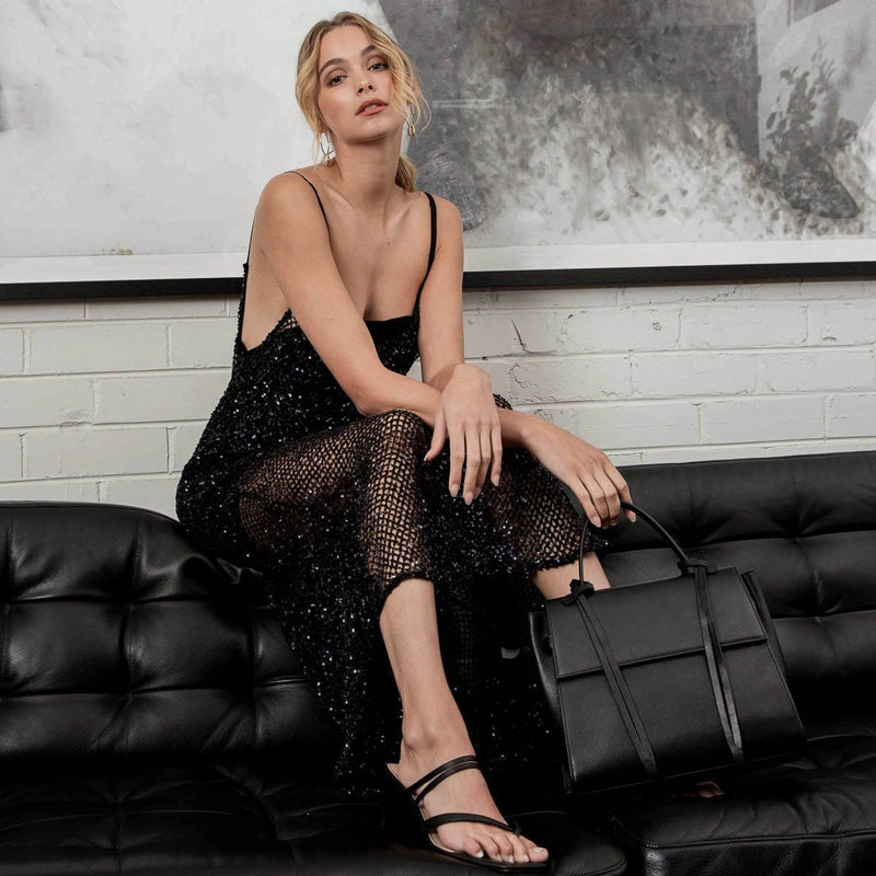 Full body shot of a young woman wearing a black slip dress sitting on a black leather couch holding a black leather handbag.