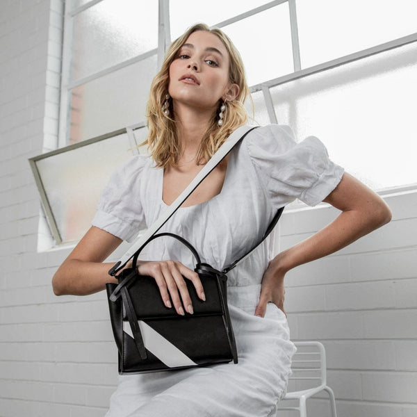 A woman wearing all white holding a rectangle genuine black and white leather work bag with black leather tassels, front flap and handle, white bag strap on one shoulder.