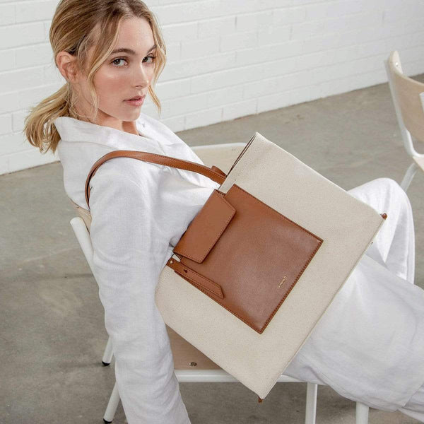 A woman wearing all white leaning back in a chair wearing the rectangle tan leather and natural canvas fabric tote bag on one shoulder.