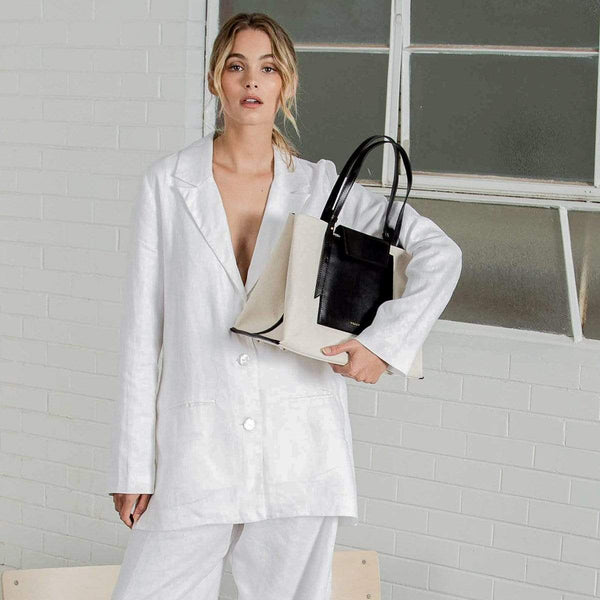 A woman wearing all white holding a rectangle black leather and natural canvas fabric tote bag with black leather handle, standing in front of a white brick wall.