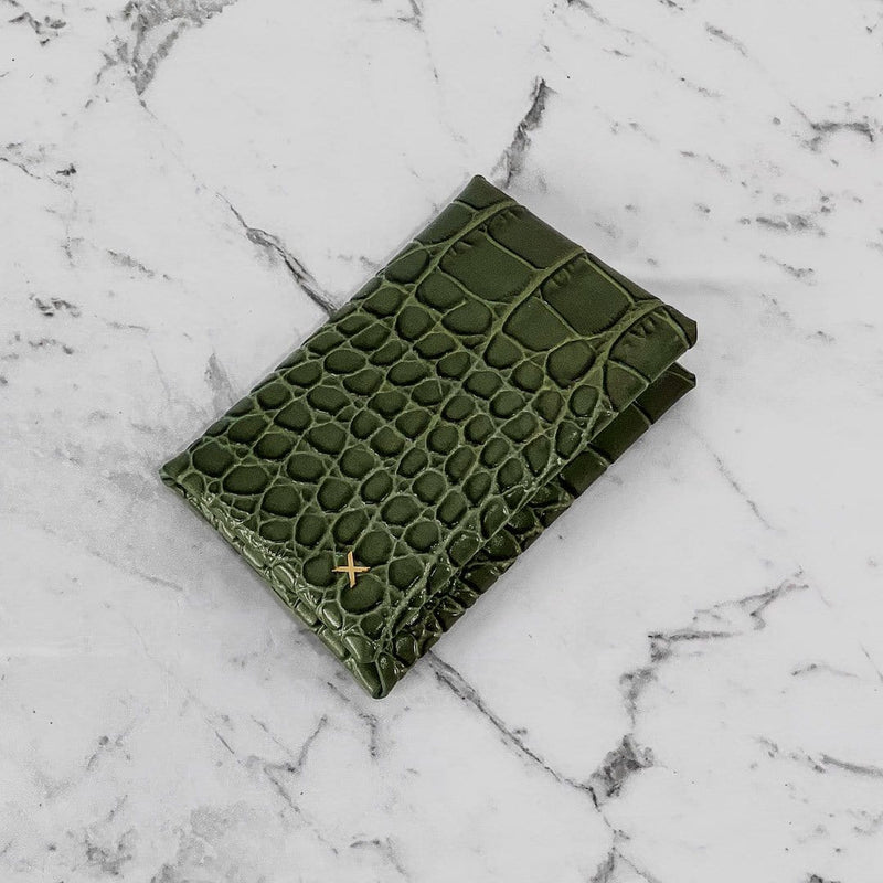 Olive croc print leather cardholder with logo X in gold hardware in the bottom corner of the cardholder, placed on a white marble background.