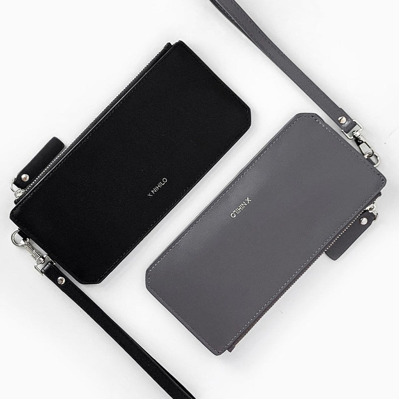 Top view of slim black leather wallet and slim grey leather wallet adjacent to each other, each with a leather strap and logo X NIHILO embossed on the surface.