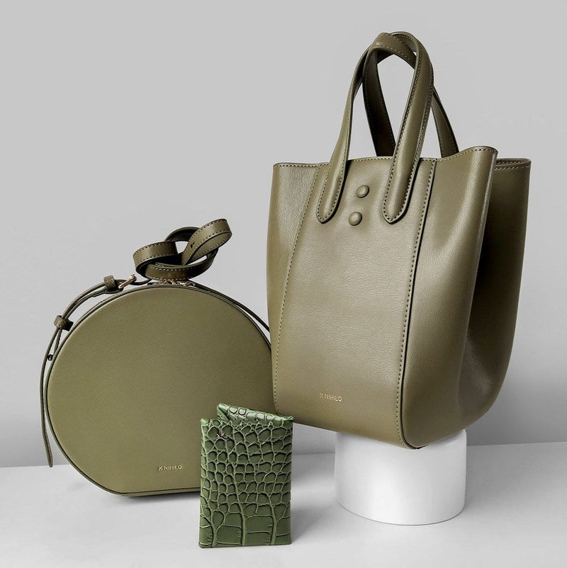 Khaki round leather shoulder bag on the left, khaki leather trapezoid handbag on the right and the olive croc print leather cardholder placed near the bottom centre.