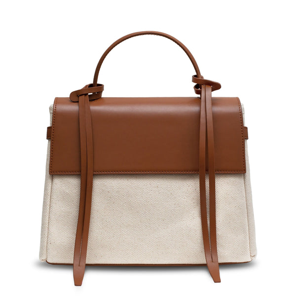 Tan leather and natural canvas fabric trapezoid bag with tan leather tassels, front flap and handle.