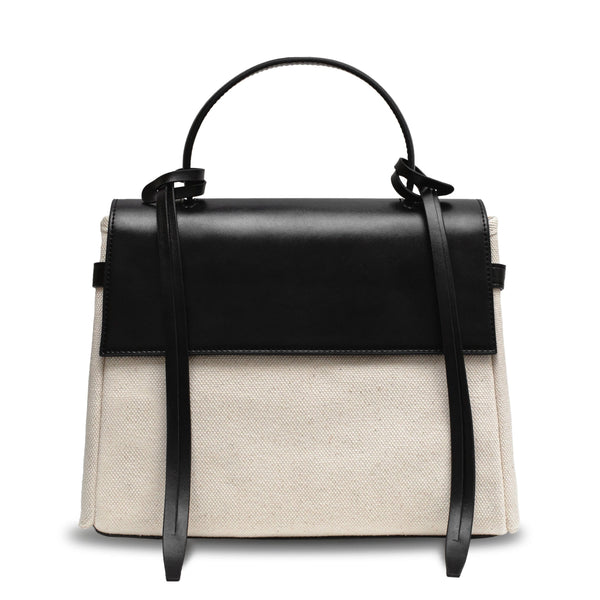 Black leather and natural canvas fabric trapezoid bag with black leather tassels, front flap and handle.
