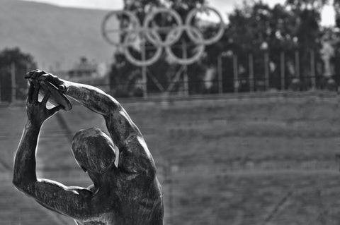 black and white olympic logo with bronze discus statue