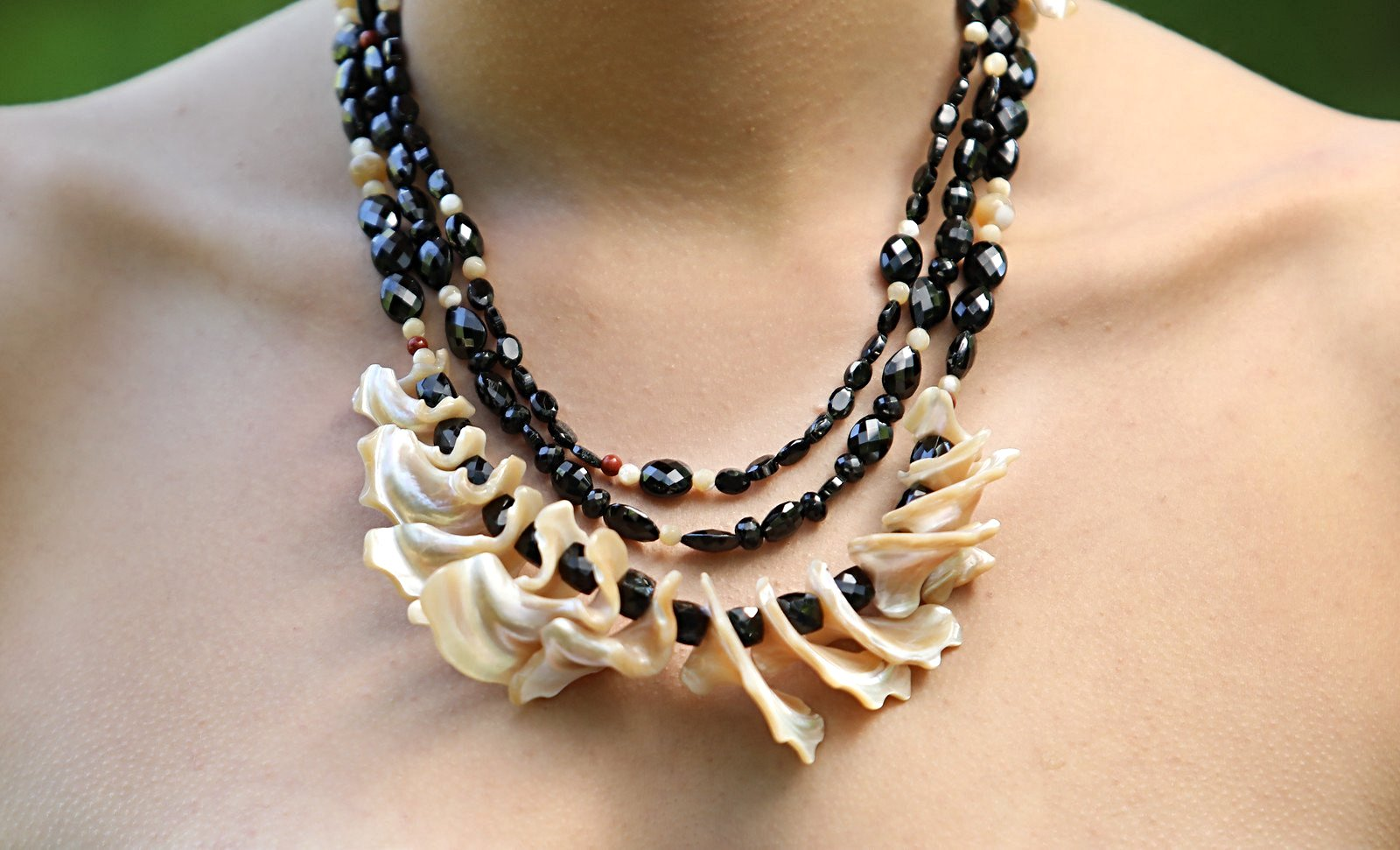 "White Orchid Studios | Made in the USA | Handcrafted couture jewelry inspired by nature. | This necklace features a dramatic three-strand bib of black spinel and mother of pearl. Look for unexpected shapes, configurations, along with pops of red jasper. This necklace ends in our silver, hand-carved vanilla bean clasp. 20"" $810"