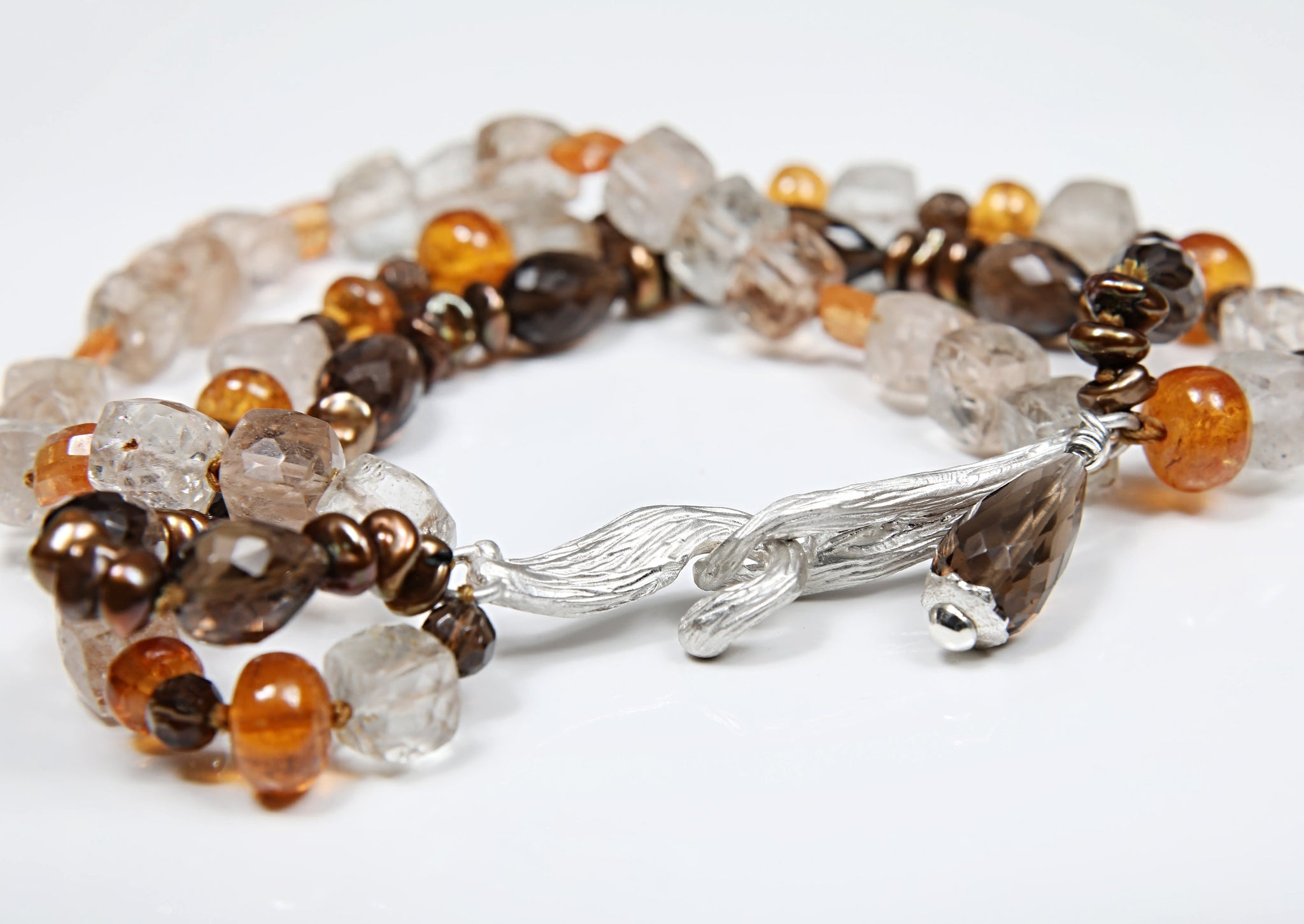"White Orchid Studios | Made in the USA | Handcrafted couture jewelry inspired by nature. | A three strand bracelet of precious topaz brought to life by smoky quartz, mandarin garnet, and bronze Keshi pearls, all brought together with our signature vanilla bean clasp in sterling. 7.75"" $757"