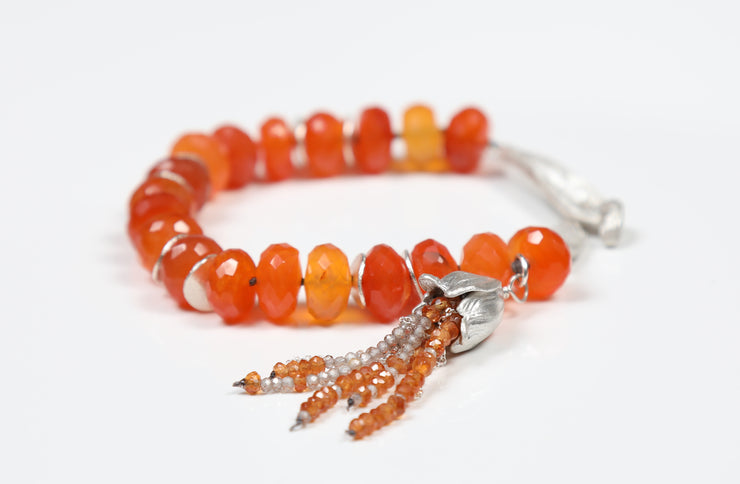 "White Orchid Studios | Made in the USA | Handcrafted couture jewelry inspired by nature. |  Faceted carnelian and our sterling spacers are enhanced by a hand-crafted tassel of carnelian, rutilated quartz, and sterling chain. Our sterling bead cap covers the tassel.  The bracelet comes together with our sterling hand-carved vanilla bean clasp, 7.5"" $791"