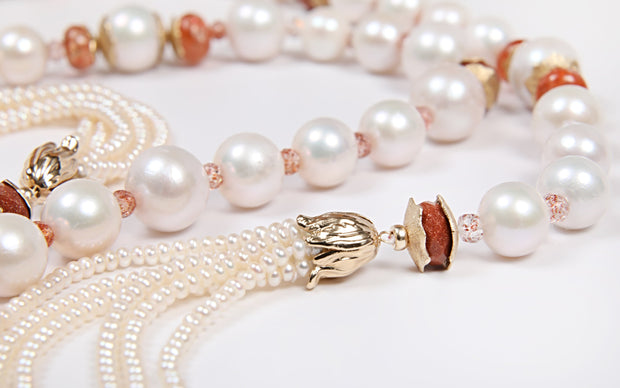 "White Orchid Studios | Made in the USA | Handcrafted couture jewelry inspired by nature. |  Off-round, freshwater, creamy white pearls with opaque and translucent sunstone as well as goldstone embraced by our custom spacers and bead caps in 14kt yellow gold. Extravagant button pearls further enhance the mood. 56"" $7820"