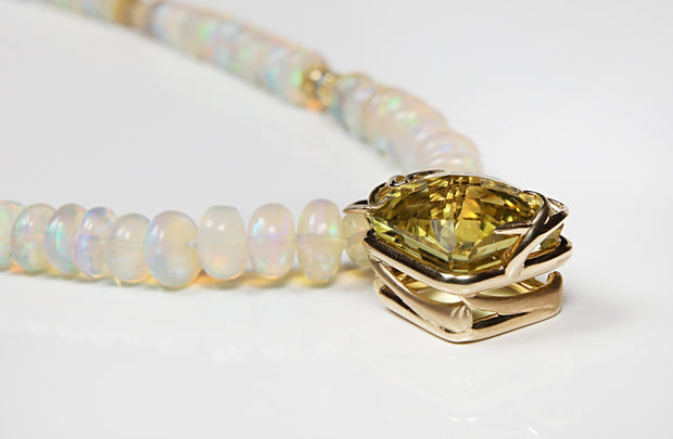"White Orchid Studios | Made in the USA | Handcrafted couture jewelry inspired by nature. |  A strand of fiery Welo opals and soothing sky blue topaz set off with 14kt yellow gold, woven spacers, our artisan-crafted logo clasp and basket with a 27.23 ct lime-lemon citrine. 16"" $5245"