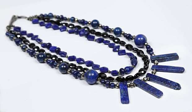 "White Orchid Studios | Made in the USA | Handcrafted couture jewelry inspired by nature. | A dramatic three-strand bib of lapis lazuli and black spinel, completed by our hand-carved, vanilla bean clasp in sterling. 20"" $760"