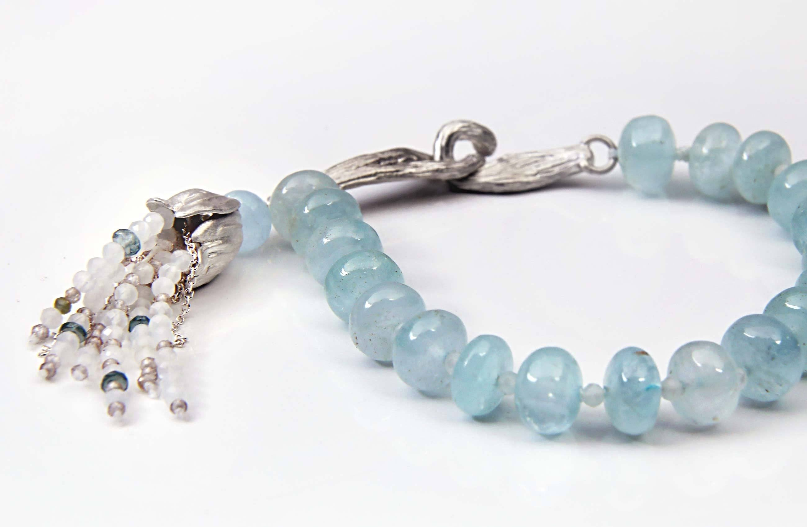 "White Orchid Studios | Made in the USA | Handcrafted couture jewelry inspired by nature. |  Polished aqua rondelles, faceted moonstone spacers and tassels are enhanced by our sterling bead cap and signature, vanilla bean clasp, 6.75"" $608"