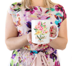 "a woman holding a white ceramic mug with a bouquet of hand painted flowers in red, pink, orange, and yellow with green leaves and stems printed on the mug. Below the bouquet the words ""Beautiful Mom"" in a gold cursive font"