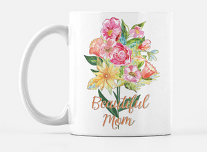 "white ceramic mug with a bouquet of hand painted flowers in red, pink, orange, and yellow with green leaves and stems printed on the mug. Below the bouquet the words ""Beautiful Mom"" in a gold cursive font"