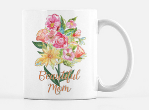 "An alternate view of the opposite side of the mug. white ceramic mug with a bouquet of hand painted flowers in red, pink, orange, and yellow with green leaves and stems printed on the mug. Below the bouquet the words ""Beautiful Mom"" in a gold cursive font"