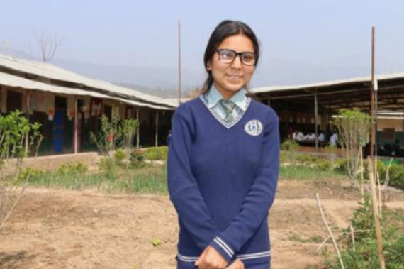 Suscila from Nepal standing outside her school smiling on a sunny day.
