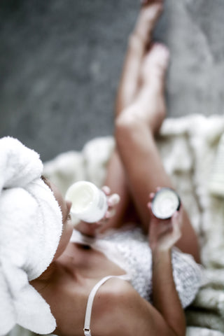Woman holding tub of body cream with hair wrapped in towel.