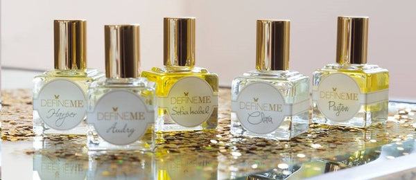 DefineMe Fragrance Oils bottles in a row on gold glitter.