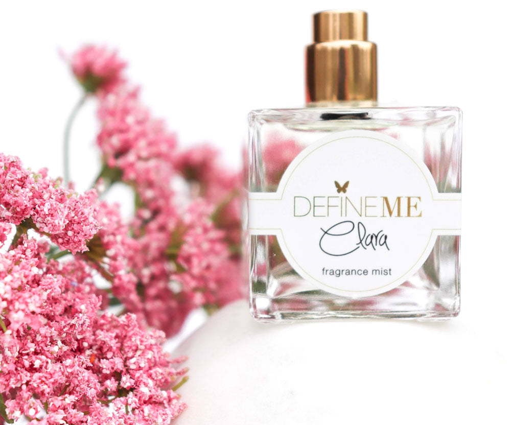 Define Me Fragrance Mist Clara surrounded by vibrant pink flowers.