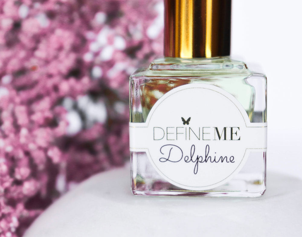 Define Me Fragrance Oil Delphine surrounded by vibrant purple flowers.