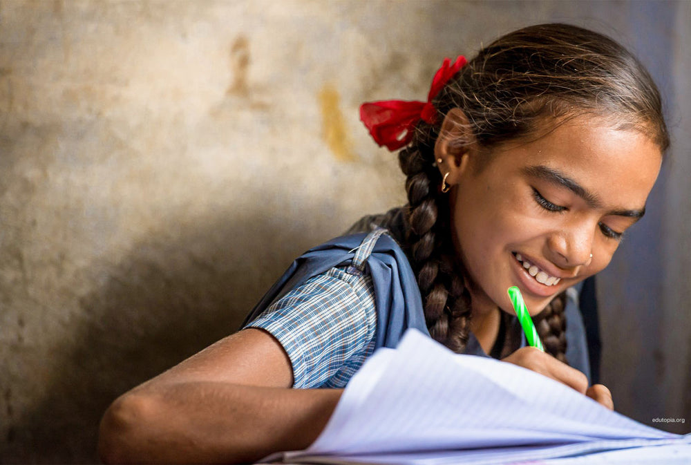 A young girl in school uniform smiling and writing in a notepad in a classroom.