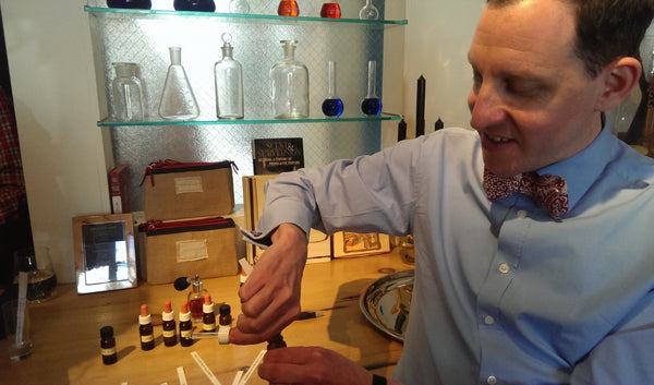 Man showing how to make perfumes in studio.