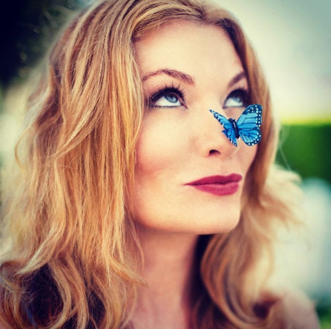 DefineMe Fragrance Founder Jennifer McKay Newton with blue flower on her nose.
