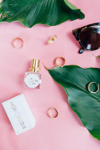 DefineMe Fragrance Clara Mist lying on pink background with fragrance box, gold rings, and sunglasses.