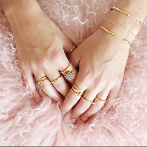 Two hands lying on pink tutu with bracelets and rings on fingers.