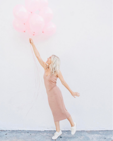 Katie Dean in pink dress and white shoes holding bunch of pink balloons.