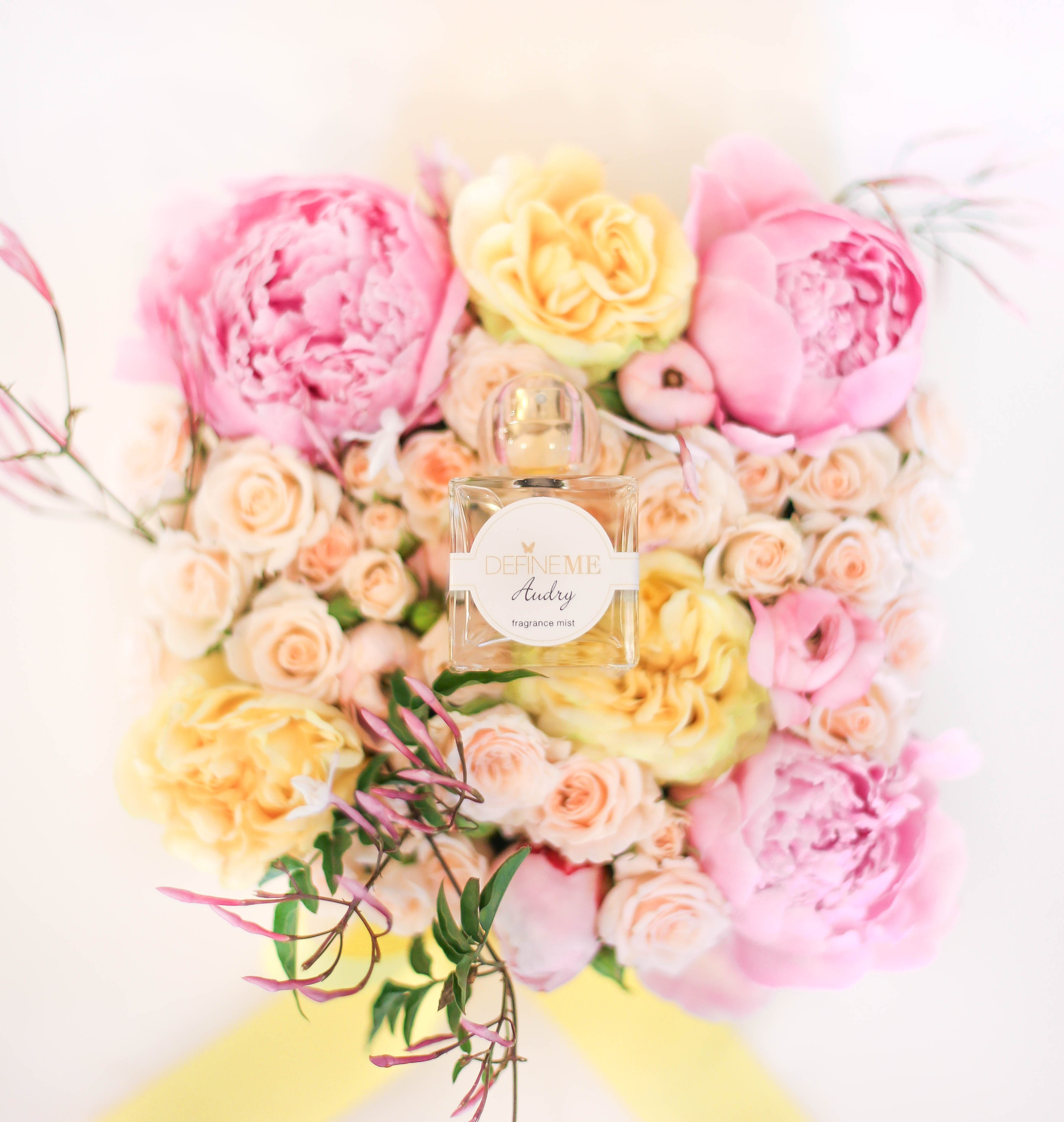 DefineMe Fragrance Audry Mist sitting atop a bunch of brightly colored pink and yellow flowers.