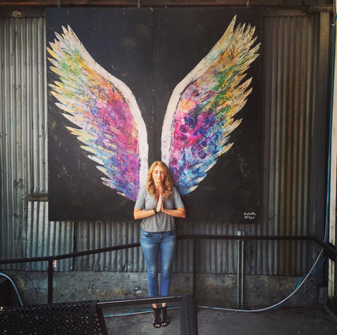 DefineMe Fragrance Founder, Jennifer McKay Newton standing in front of colorful painted wings on a wall and holding hands in prayer.
